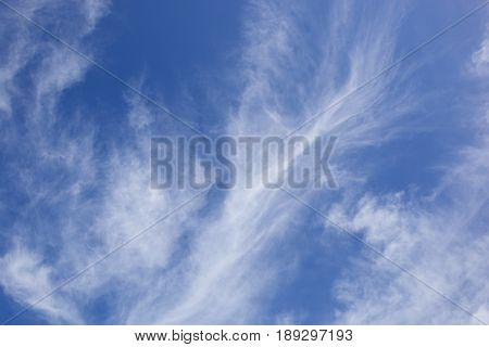 a blue sky background image with white wispy cloud in summer