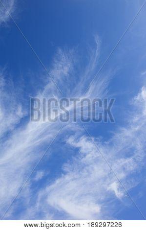 a blue sky background with white wispy cloud
