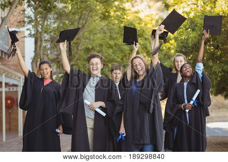 Portrait of graduate school kids standing with degree scroll and mortarboard in campus