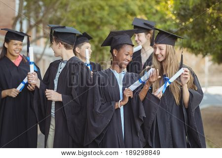 Smiling graduate school kids standing with degree scroll in campus at school