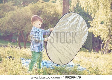 Toddler boy assists the photographer with reflector. Little helper concept