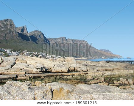 CAMPS BAY, CAPE TOWN, SOUTH AFRICA, WITH HUGE BOULDERS IN THE FORE GROUND AND A MOUNTAIN IN THE BACK GROUND 22loiux