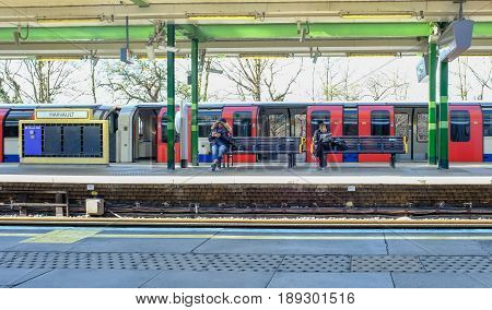 Hainault Ilford Essex England: March 3 2017: Platform at Hainault tube station with two passengers sitting reading.