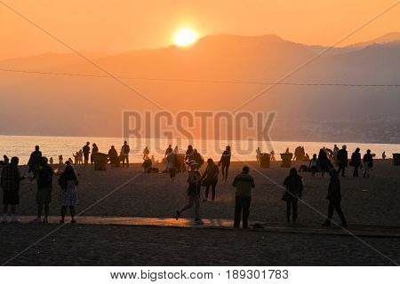 June 1, 2017 in Santa Monica, CA:  Sun setting over the Santa Monica Mountains and the Pacific Ocean taken on the crowded Santa Monica Beach, CA where people can enjoy relaxing, swimming, and watching the sunset