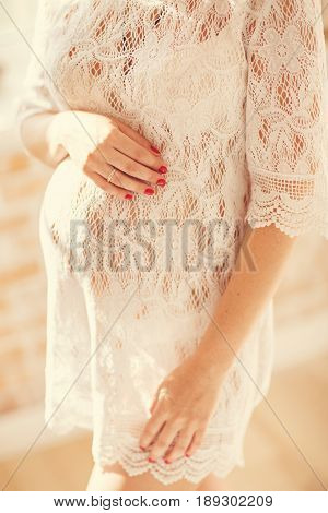 pregnant woman in a lace dress stands by the window
