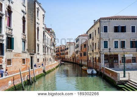 VENICE, ITALY - May 18, 2017.View of water street and old buildings in Venice on May 18, 2017. its entirety is listed as a World Heritage Site, along with its lagoon