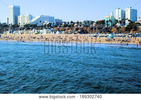June 1, 2017 in Santa Monica, CA:  People relaxing and swimming at the beach with Highrise Buildings beyond during the crowded summer season taken at Santa Monica Beach, CA where the public can enjoy the beach and recreational activities
