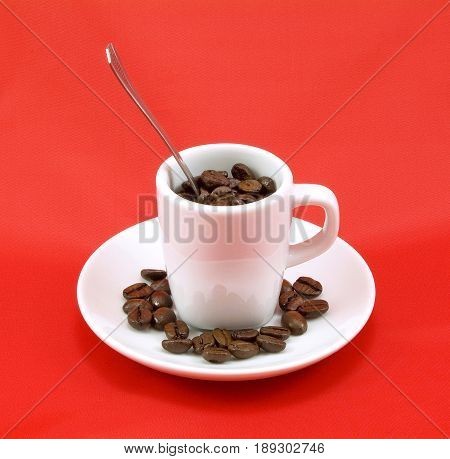 Brown roasted coffee beans in white cup, with red background