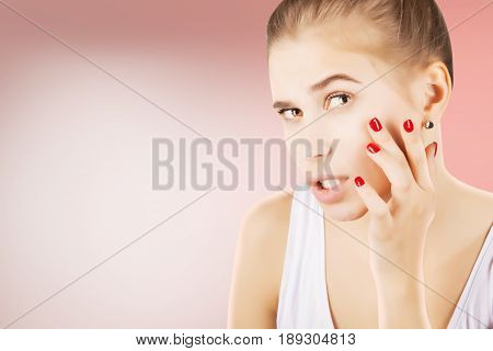 young girl looking to her skin with astonishment