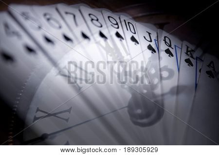 Playing cards in succession with clock hands on background multiexposition