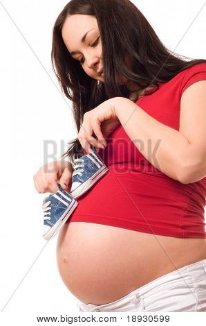 A pregnant woman holding baby shoes
