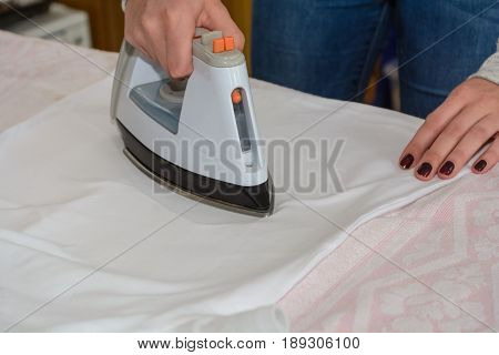 Woman ironing with steam iron on ironing board