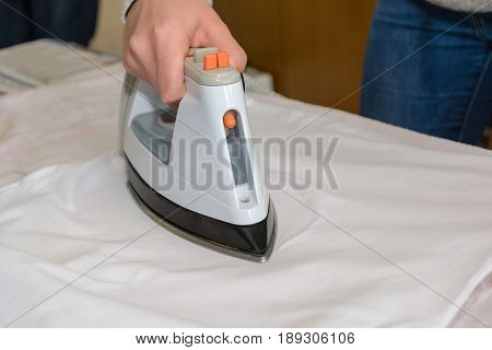 Iron on the ironing table with steam iron