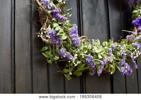 Vertical of purple and green floral grapevine wreath against black think planked wooden door