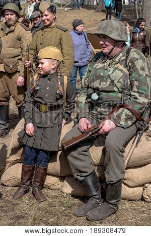 Gatchina, Russia - May 7, 2017: Historical reconstruction of the battles of World War II. German soldiers and the girl in the form of the Soviet army rest and laugh after reconstruction.