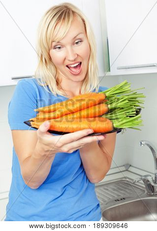 beautiful blond woman with carrot at home