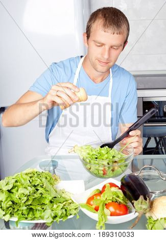 handsome young man cooking salad at home