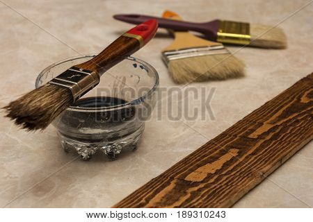 Treatment of wood by brush and dark wood stain