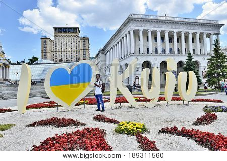 KYIV UKRAINE - CIRCA MAY 2017: Celebration 1535-th Day of Kyiv. Guest African youth stands near stylized banner I LOVE KYIV for image taking