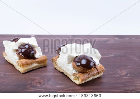 Two delicious chocolate and chantilly french gateau cake Tranche Saint Honore on a natural ipe wood board - white background poster