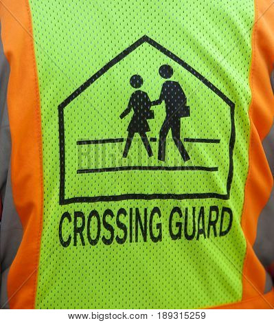 Crossing guard symbol on safety vest up close.