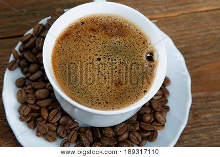 Cup With Coffee On The Table Next To Coffee Beans