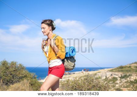 Young woman carrying a backpack on an excursion