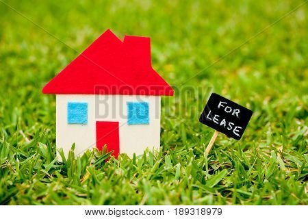 House - Home - For Lease blackboard on grass background