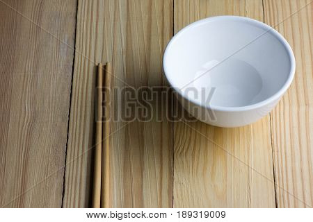 ceramic white bowl and chopsticks on the wooden table
