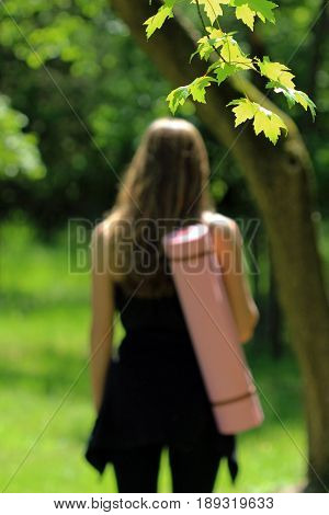 Focus on nature tree leaves with blurred person carrying yoga mat in background.