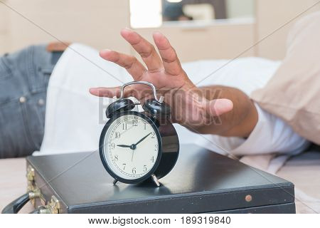 Hand of a man reaching the alarm clock on the briefcase placed it on the bed.