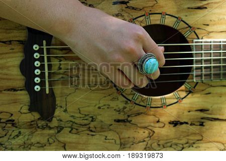 Female hand strumming acoustic guitar close up with turquoise ring.