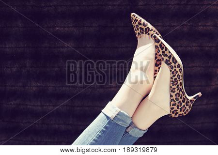 Female legs up in the air wearing leopard print high heels and blue jeans.