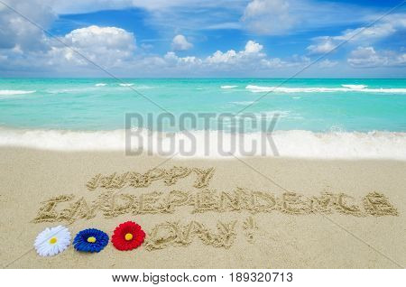 Independence USA background with flowers of american flag colors on the sandy beach near ocean