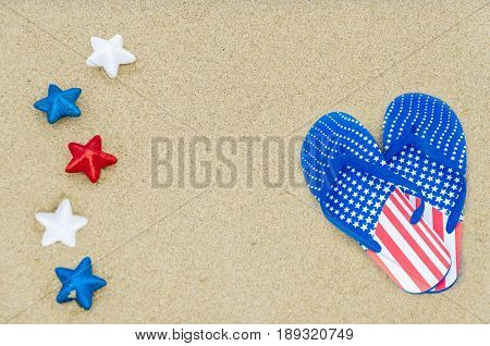 Patriotic USA background with flip flops and white red and blue stars on the sandy beach