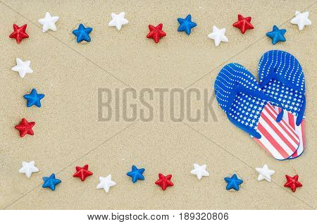 Patriotic USA background with flip flops and stars on the sandy beach