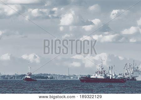 Two tug ships are accepting cargo vessel at Daugava river