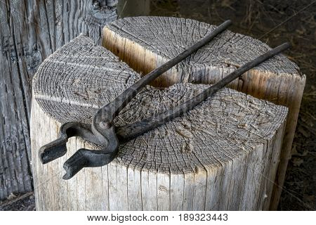 Vintage blacksmith pliers on wooden log in an old workshop