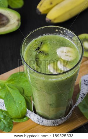 Green smoothie with spinach,banana, kiwi. Fresh and healthy green cocktail on a dark background.
