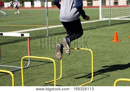 A high school male athlete bounds over yellow hurdles on a green turf field during practice