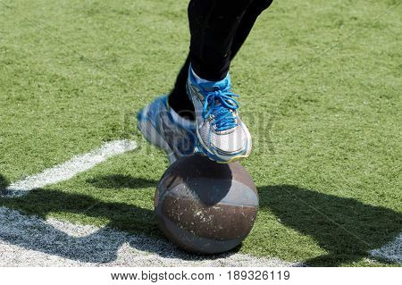 An athlete tries to stand on a medicine ball and falls on a green turf field