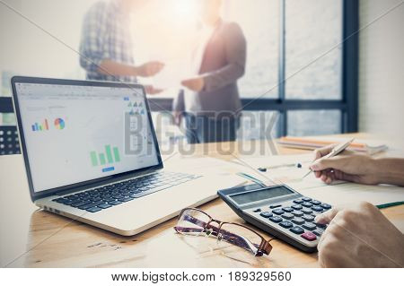 Business People Present Turnover Graph Chart Paper And Doing Calculator Math For Ceo Of Company With