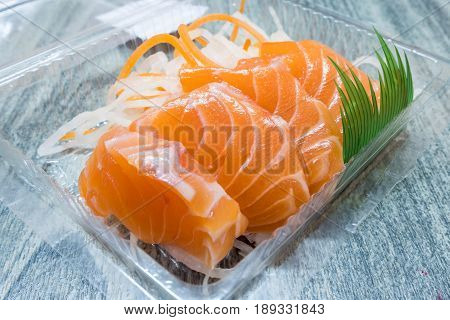 Close up of salmon raw sashimi pack in clear plastic box on wooden table. Select focus