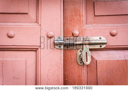 old bolt on a retro wooden door is unlock.