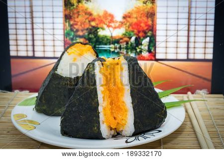 Japanese onigiri sushi on dish and traditional mat with egg shrimp and open door autumn background. The symbolic food of Japan.