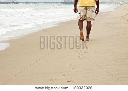 African American man walking on the beach. Looking at the ocean.