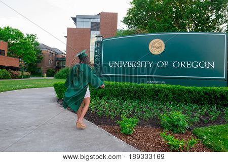 EUGENE, OR - MAY 22, 2017: Female college student poses for graduation photos at the main entrance sign on campus at the University of Oregon in Eugene.