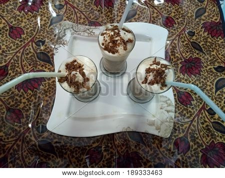 Cold coffee drink frappe with Vanilla ice cream and caramel syrup ,straws and grains of coffee with chocalate chips