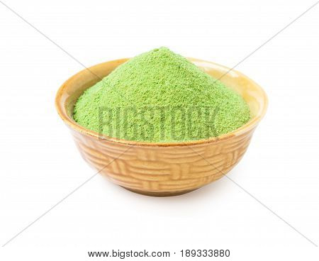 Green matcha tea powder in bowl isolated on white background with clipping path