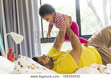 Father lay down and raising little girl on the bed